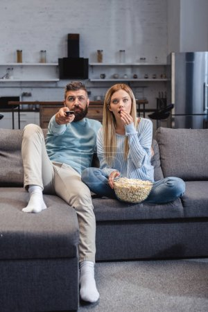 Photo pour Couple assis sur le canapé avec pop corn et regarder film - image libre de droit
