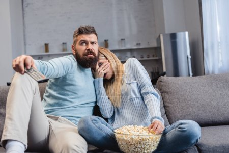 Couple sitting with popcorn and watching scary movie
