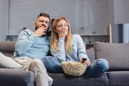 Photo for Sleepy couple sitting on sofa with popcorn - Royalty Free Image