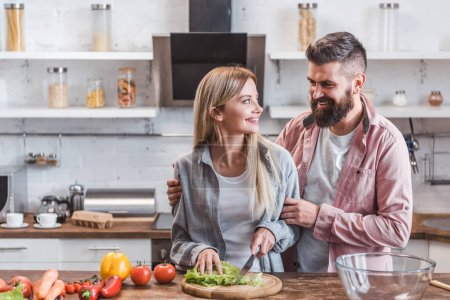 Cheerful and smiling couple preparing dinner in kitchen