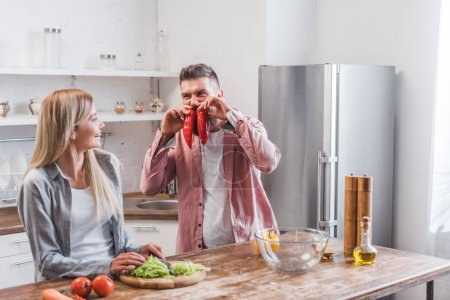 Cheerful husband playing with vegetables near wife