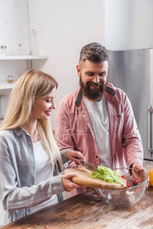 Photo for Couple standing in kitchen and adding salad leaves in bowl - Royalty Free Image