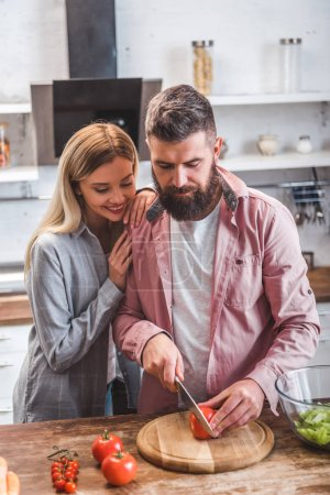 Photo for Husband and wife standing in kitchen and preparing salad - Royalty Free Image
