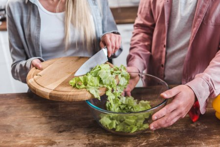 Photo for Cropped view of woman adding salad leaves and man holding bowl - Royalty Free Image