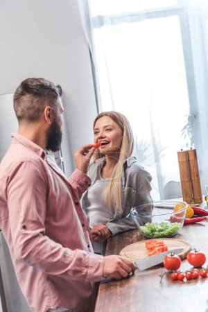 Husband feeding wife and standing in kitchen