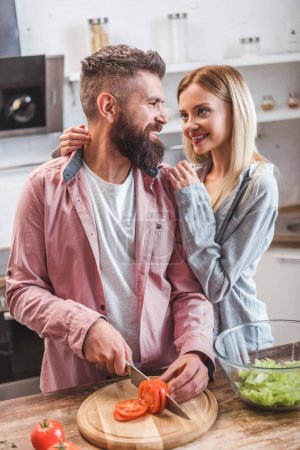 Photo for Cheerful couple preparing dinner in kitchen - Royalty Free Image