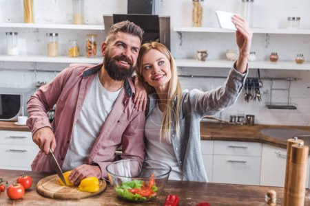 Photo for Cheerful couple taking selfie on smartphone - Royalty Free Image