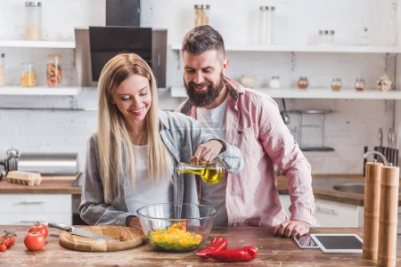 Beautiful wife standing with husband in kitchen and adding oil in salad