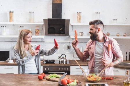 Photo pour Couple drôle de jouer avec des légumes pendant la cuisson dîner à la table en bois - image libre de droit