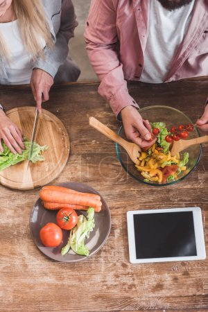Photo for Cropped view of couple cooking vegetable salad with digital tablet at wooden table - Royalty Free Image