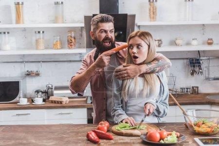 Photo pour Homme drôle mettant carotte près de tête de femme tout en peur fille cuisine dinatoire - image libre de droit