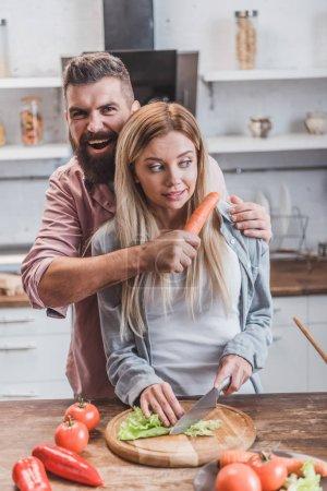 Photo pour Homme drôle mettant carotte près de la gorge de femme tout en fille cuisine dinatoire - image libre de droit