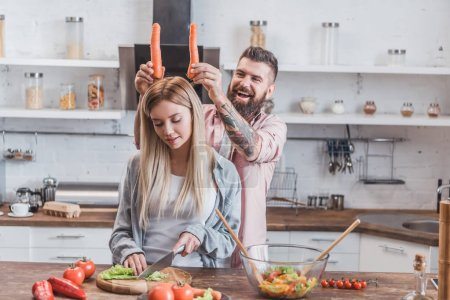 funny man putting carrots on woman head while girl cooking dinner
