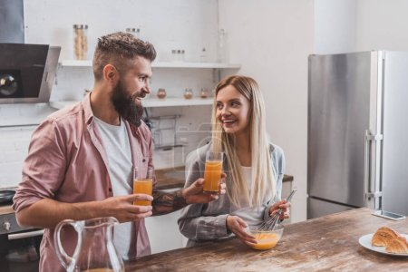 Photo for Young smiling woman preparing breakfast while handsome man holding glasses with juice - Royalty Free Image