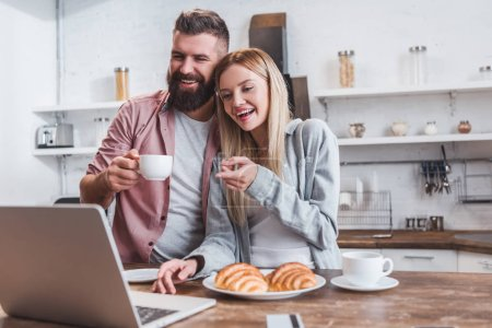 smiling woman pointing at laptop screen while man drinking coffee