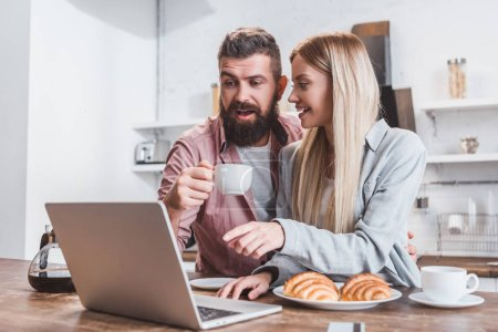 cheerful couple having breakfast and using laptop in morning