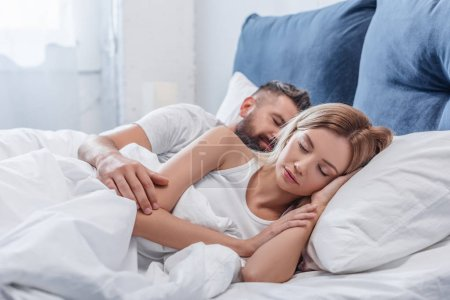 beautiful blonde woman sleeping in bed with boyfriend in morning
