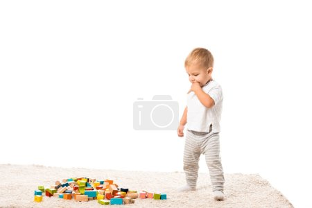 toddler boy standing and looking at multicolored wooden building blocks on carpet isolated on white
