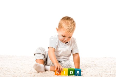 cute toddler boy playing colored cubes with letters on carpet isolated on white