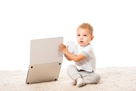 Photo for Cute toddler boy sitting on carpet and holding laptop isolated on white - Royalty Free Image