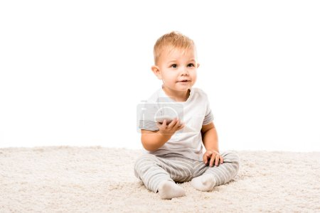 Photo for Adorable toddler boy with smartphone sitting on carpet isolated on white - Royalty Free Image