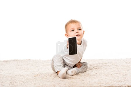 nice toddler boy sitting on carpet and showing smartphone screen isolated on white