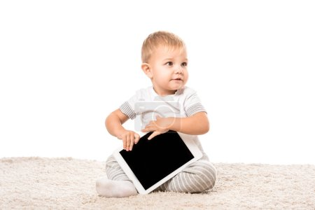 Photo for Nice toddler boy sitting on carpet and holding digital tablet isolated on white - Royalty Free Image