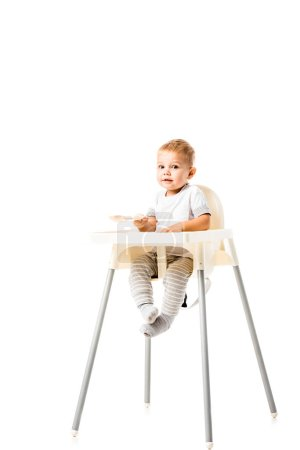 Photo for Cute toddler boy sitting in highchair and looking at camera isolated on white - Royalty Free Image