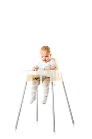 Photo for Cute toddler sitting in highchair isolated on white - Royalty Free Image