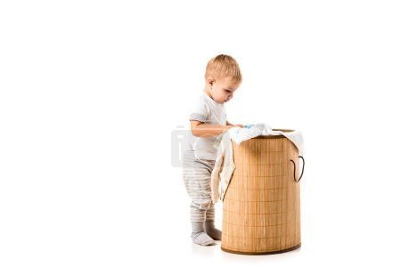 toddler boy looking into wicker laundry basket isolated on white