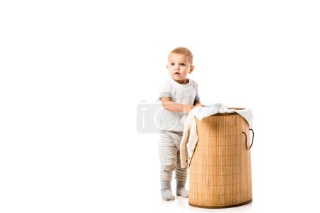 nice toddler boy standing near wicker laundry basket isolated on white