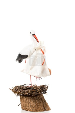 decorative stork holding in beak baby nappy and standing in wicker nest isolated on white