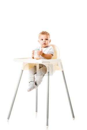 adorable toddler boy holding baby bottle and sitting in highchair isolated on white