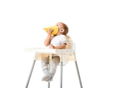 Photo pour Tout-petit garçon tenant chapeau de fête jaune et assis dans une chaise haute isolé sur blanc - image libre de droit
