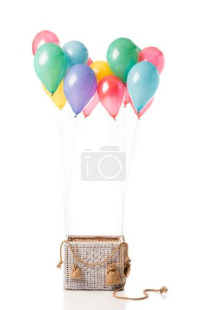 wicker basket with multicolored balloons isolated on white