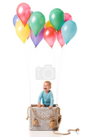 toddler boy crying and standing in wicker basket with multicolored balloons isolated on white
