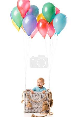 Photo pour Tout-petit garçon souriant et debout dans un panier en osier avec des ballons multicolores isolés sur blanc - image libre de droit