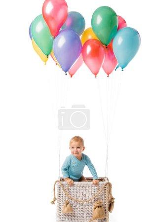 Photo pour Petit garçon souriant dans le panier avec des ballons multicolores isolés sur blanc - image libre de droit
