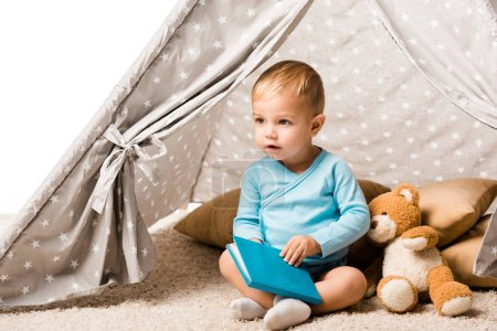 Photo pour Tout-petit garçon tenant livre bleu et assis dans wigwam avec des oreillers et ours en peluche isolé sur blanc - image libre de droit