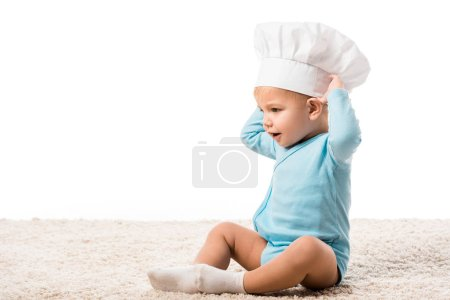 toddler boy in chefs hat with hands on head sitting on carpet isolated on white