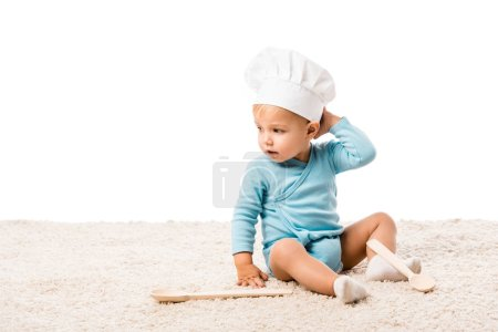 toddler boy in chefs hat sitting on carpet near two big wooden spoons isolated on white