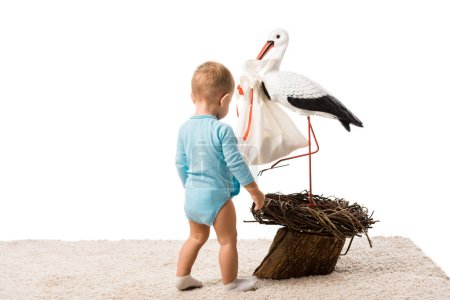 cute toddler boy in blue bodysuit standing on carpet and looking at big decorative stork isolated on white