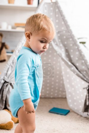 close up view of cute toddler boy in blue bodysuit standing near grey baby wigwam