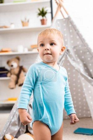 cute toddler boy in blue bodysuit standing near grey wigwam in nursery room