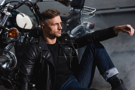 handsome biker in leather jacket relaxing by motorcycle in garage