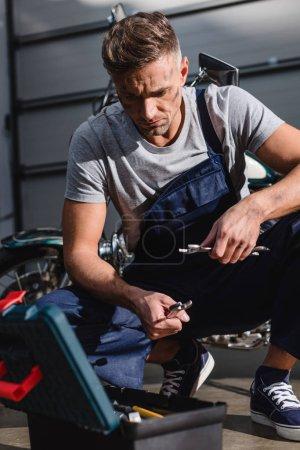 Photo pour Beau mécanicien cueillette clés de fixation moto dans le garage - image libre de droit
