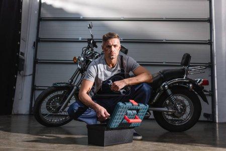 Foto de Apuesto mecánico enfocado teniendo llaves de la caja de herramientas para la fijación de motos en garaje - Imagen libre de derechos