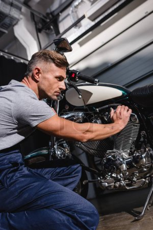 handsome adult mechanic fixing motorcycle engine in garage