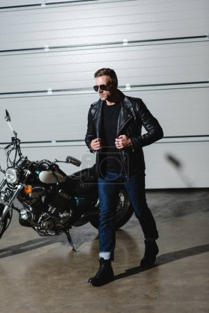 cool guy in sunglasses and leather jacket walking in garage