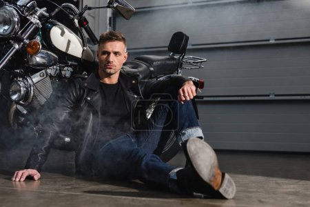 handsome guy sitting on ground by motorcycle in garage